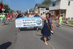 Buffalo-Niagra union members march in a parade carrying a banner reading A United Voice Fighting for the Working Class