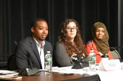 An African-American man, a white woman, and a white woman wearing a Habib, sit at a speaker table on stage engaging with the audience.