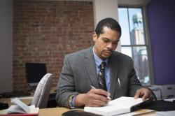 Researcher sits with pen poised over open book