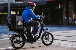Food delivery worker on a bike wearing a mask