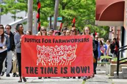 Protest marchers carry a banner reading, Justice for Farmworkers, the time is now.