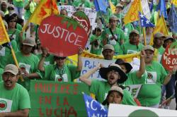 Crowd of protestors in green shirts and hats holding a sign reading Justice
