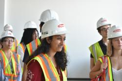 Ashni Verma stands with a group of High Road Fellows wearing hard hats and listening to a speaker.