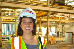 Emily Bramhall wears a hard hat and reflective vest and holds floor plans as she visits a Buffalo construction site.
