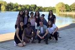 10 students pose in front of small lake