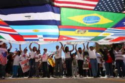 Protestors stand under a large canopy of flags of the world sewn together