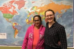 Olivia Smith stands with unidentified woman in front of World map