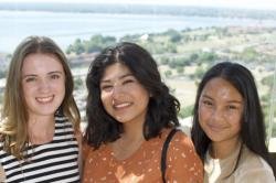 Three women smile into the camera with farm fields and a lake in the background