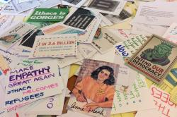 Scattered pile of bumper stickers, postcards, notes reading, Defend our Democracy, Anne Frank, Make Empathy Great Again - Ithaca welcomes refugees, etc.