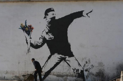 Banksy illustration showing a masked dissident in an aggressive stance about to throw a bouquet of flowers