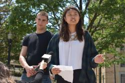 Wendy Lau stands with notes in hand and an unidentified man behind her in support as a reporter holds a mike up to her.