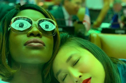 Two women sit close, one with eyes closed and her head resting on the shoulder of the second, whose glasses have paper eyes pasted to their lenses.
