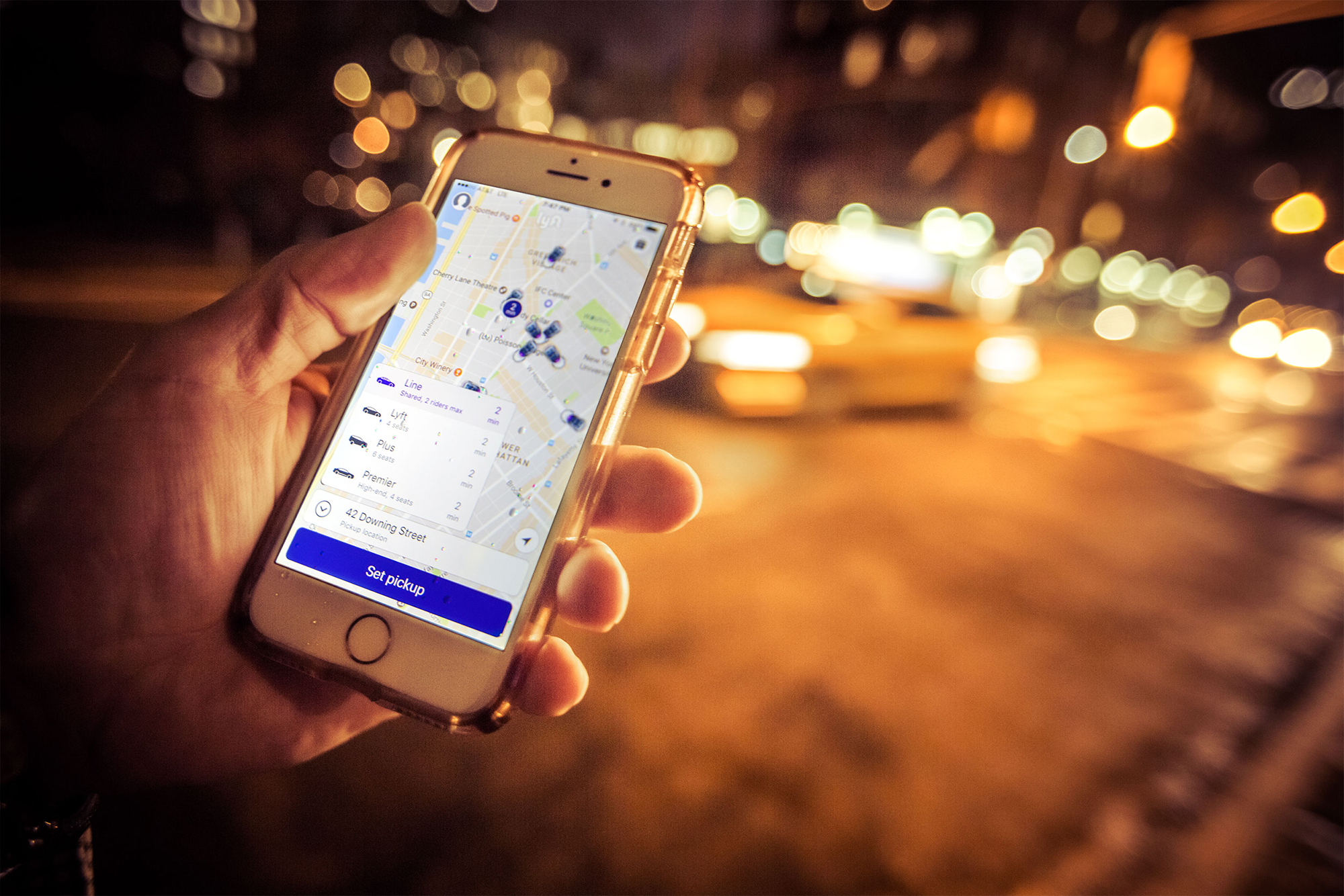 Photo: Hand with a smart phone with traffic in the background