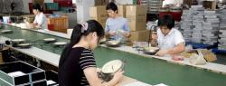 International factory workers assembling clocks