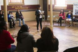 A woman speaks at the center of a meeting of women day laborers in Williamsburg