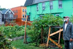 West Side resident Bob Jahnke, a longtime member of the PUSH Community Development Committee, walks through one of the community gardens in his neighborhood.