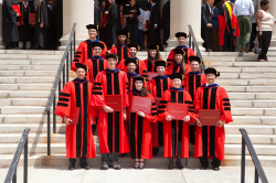 PhD students wearing red robes at Commencement